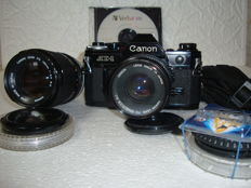 CANON AE-1 black housing + CANON FD 50 mm f/1.8 lens + CANON FD 135 mm/3.5 + various accessories.
