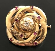 Swirl-shaped  brooch in 18 kt yellow gold centred around a traditionally cut diamond E/VVS (.1 ct) and decorated with .24 ct of rubies.