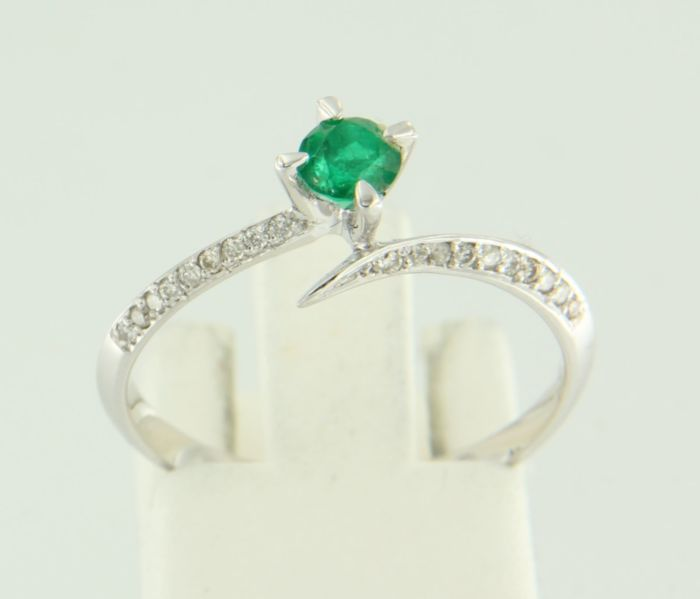 14 kt white gold wavy ring centrally  set with a 0.32 carat, brilliant cut emerald and 19 brilliant cut diamonds, approx. 0.08 carat in total, ring size: 17.25 (54)