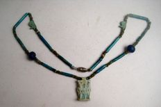 Chain of faience mummy beads, 2 Horus or Wedjat-eyes and a triad-amulet - 50 cm.