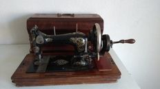 Antique hand sewing machine decorated with golden engravings and original wooden cover / key, early 20th century