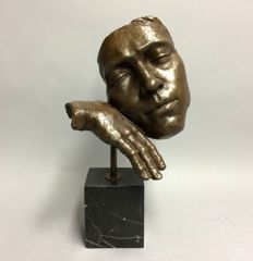 Bronze sculpture of a face resting on a hand
