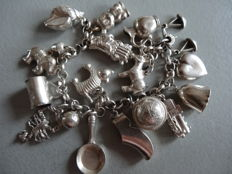 Silver bracelet with 18 charms on an antique Jasseron chain