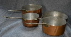 Four copper pans with brass handle