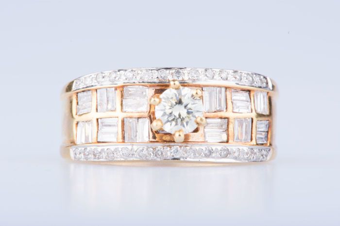 18 kt yellow gold ring 1 diamond of approx.  0.30 ct 30 diamonds approx. 0.30 ct in total 24 baguette-cut diamonds approx. 0.48 ct in total