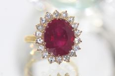 18 kt gold entourage ring, set with a ruby and sapphires, size 52