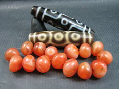 Two 9 eye agate dzi beads together with fifteen carnelian prayer beads - Himalayan regions - third quarter of the 20th to early 21st century.
