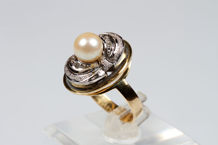 White and yellow gold ring with a central pearl surrounded by diamonds