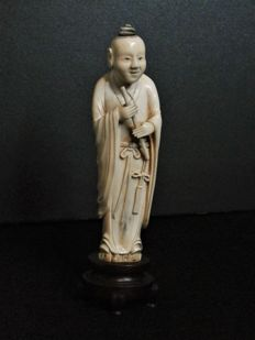 A very detailed carved ivory statue of a man in long ropes - China late 19th century