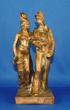 Antique bronze statue of a man and a woman in traditional French costume
