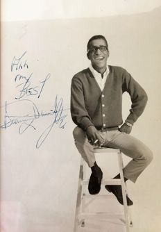 Sammy Davis Jr, USA celebrity and  forfighter stopping racial separation, sanger and entertainer: original sixties Photo smoking on a chair with handwritten tekst and autograph