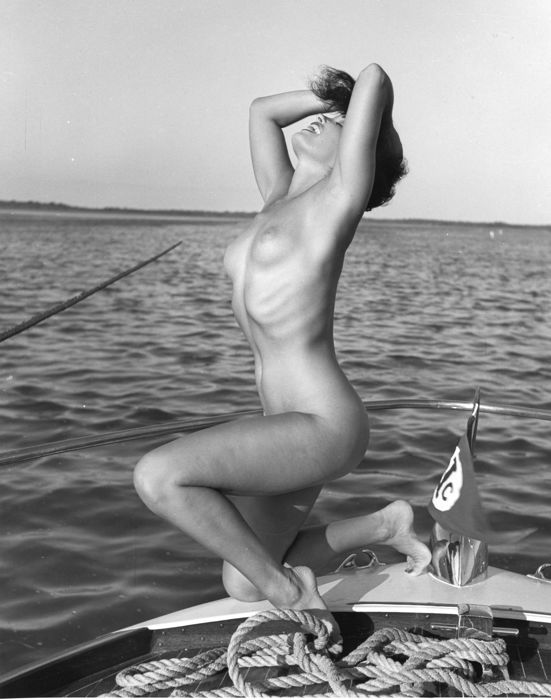 Bunny Yeager - Bettie Page, erotic pose in ship, 1980.