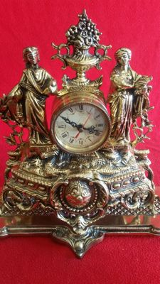 Spectacular clock in bronze alloy, carved with the romantic figure of a man and a woman and crown of a vase. French style. 20th century