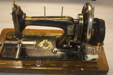 Sewing machine with a wooden dust cover, early 20th century