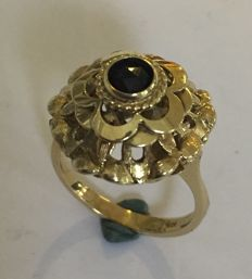 Gold cocktail ring with a garnet stone