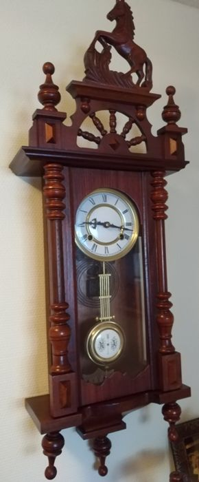 An antique walnut horse's regulator with a mechanical German timepiece