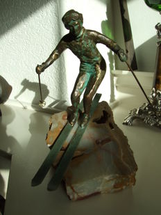 Bronze statue of a skier attached on natural stone basement