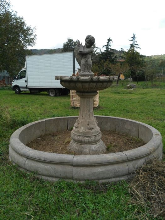 Large sized fountain, in chiselled grey sandstone, with a wide basin, a column, a second smaller basin and a putto playing with a fish - Italy, 21st century