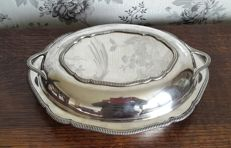 lot 691 - Antique serving dish with cover and handles. In English Silver Plated metal, with grecque trims - dimensions: h 8x29 cm - England, 1900s