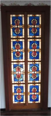 Door stained glass - prominently exuberant relief, and bold use of colour similar to opal stones - divided into eight compartments in a wooden door frame