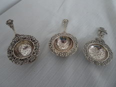 3 pieces of Dutch silver tea strainers, including one with a glass drip tray with a Dutch silver drip tray
