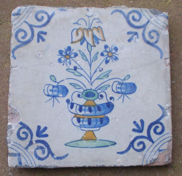 Antique polychrome tile with a depiction of a flower pot with oxen head corner motif