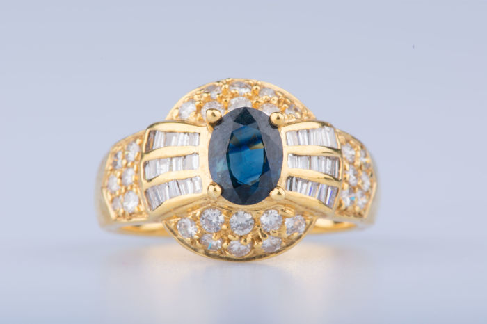 18 kt yellow gold ring with 1 oval sapphire approx. 0.70 ct, 12 diamonds approx.  0.24 ct in total, 16 diamonds approx.  0.48 ct in total, 32 baguette-cut diamonds