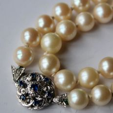 Antique necklace with genuine sea/salty Japanese Akoya pearls (7,3-7.7mm.) and white Gold handcrafted reach decorated clasp with 7 light blue natural Sapphires.