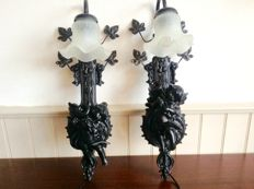 A pair of ornate wall lamp fittings with cherubs