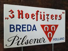 Old advertising sign 'Drie Hoefijzers Pilsener Breda'.