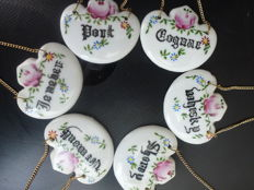Old Porcelain bottles hangers with text including cognac, whisky