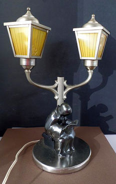 Bedside lamp representing a man reading a book under the lamps
