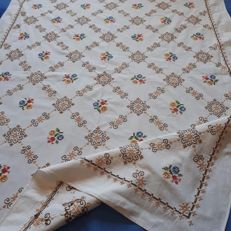 Colourful hand embroidery tablecloth in cross stitch.