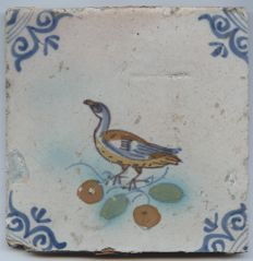 Antique polychrome tile, with a decoration of a bird