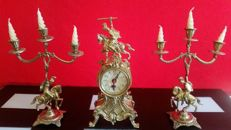 Three-pieces set of bronze alloy clock consisting of a pendulum and a couple of tripod candle holders shaped as riders on horseback