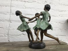 Bronze sculpture of three dancing girls