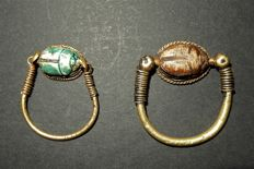 A set of 2 Egyptian gold swivel rings with glazed steatite scarabs. -28 and 22mm