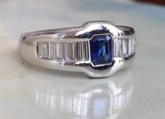 White gold 18 kt entourage men's band ring with centrally a sapphire of approx. 0.70 ct flanked by baguette cut diamonds of approx. 1.25 ct, H/VS