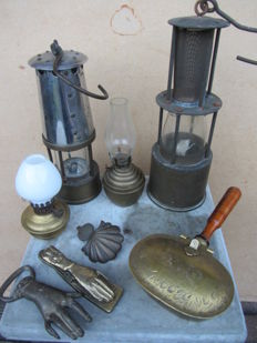Eight various items including: miners lamps, oil lamps, brass door knocker, letter clamp in the shape of a hand - First half of the 20th century, France and the Netherlands