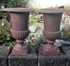 Two heavy cast iron vases with rusty patina