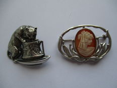 An Art Nouveau cameo brooch, and a kitten-in-the-cup brooch, both in silver.