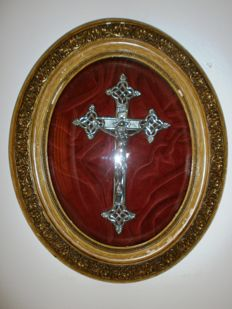 Crucifix plaque behind oval glass.
