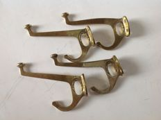 A set of 4 Art Deco coatrack hooks in brass