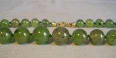 Nephrite jade necklace with beads arranged by size and a gold clasp -- circa 1930–'35