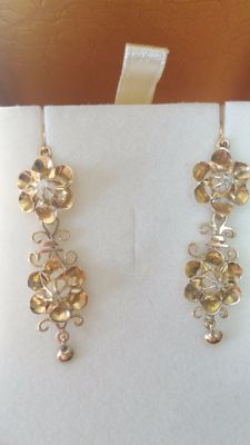 18 kt gold with small diamond rosettes in the centre of the flowers.