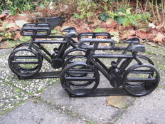 Two cast iron bicycle stands shaped like a bicycle