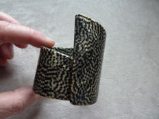 Lot 29 - Old plastic cuff, black and grey with golden reflections