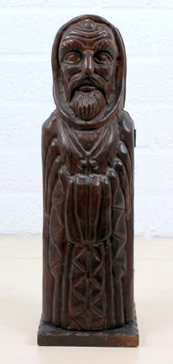 Antique wooden statue of a clergyman with room for a bottle