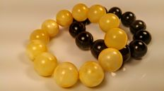 Set of 2 vintage Baltic Amber round modified beads bracelets in egg yolk and black colour, 80 grams