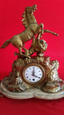Fantastic clock in alloy of solid bronze, with the carved figure of a beautiful Mustang with a lion, being its prey. Baroque Style. 20th century